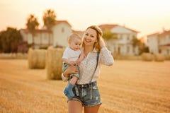 Une belle jeune blonde de mère en denim court-circuite tenir un petit Photos libres de droits