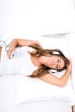 Une belle jeune femme écoutant dans le lit la musique Photographie stock