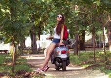Une belle jeune femme avec des lunettes de soleil se reposant sur un scooter Image libre de droits