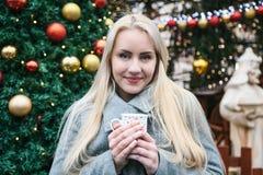 Une belle jeune femme blonde boit d'une tasse une boisson chaude image libre de droits
