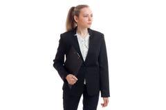 Une belle jeune femme dans un costume noir semble partie et garde la Tablette Images stock