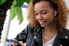 Une belle jeune femme de couleur moderne, dans une veste en cuir avec des airpods dans son oreille, écoute la musique Afro-améric images stock