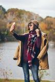 Une belle jeune femme de sourire heureuse en parc d'automne Photographie stock libre de droits