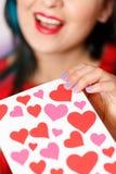 Une belle jeune femme prend une carte avec des coeurs avec une déclaration de l'amour Jour du `s de Valentine image stock