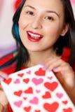 Une belle jeune femme prend une carte avec des coeurs avec une déclaration de l'amour Jour du `s de Valentine photo libre de droits