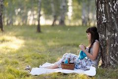 Une belle jeune femme se penchant contre un arbre tricote Image libre de droits