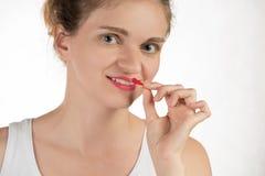 Une belle jeune fille applique un rouge à lèvres rouge liquide persistant Photo libre de droits