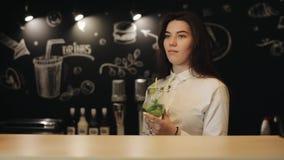 Une belle jeune fille avec de longs cheveux bruns buvant un peu de mojito à un compteur de barre banque de vidéos