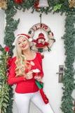 Une belle jeune fille blonde dans le chapeau d'une Santa se tient à l'entrée principale décorée d'une guirlande et des branches d photos libres de droits