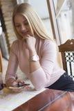 Une belle jeune fille boit du thé dans un restaurant et l'apprécie photographie stock
