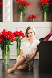 Une belle jeune fille dans un peignoir s'assied sur le plancher dans le studio avec des bouquets des tulipes photos libres de droits