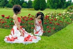 Une belle jeune fille dans un regard rouge de robe dans le miroir Photo stock