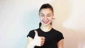 Une belle jeune fille dans un T-shirt noir est souriante et montrante le pouce vers le haut de regarder la caméra banque de vidéos