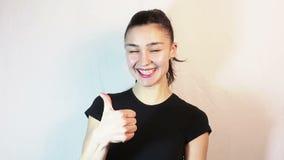Une belle jeune fille dans un T-shirt noir est souriante et montrante le pouce vers le haut de regarder la cam?ra banque de vidéos