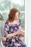 Une belle jeune fille dans une robe colorée lumineuse s'assied dans un fauteuil par la fenêtre et regarde pensivement la rose Image stock