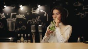 Une belle jeune fille essayant un cocktail de mojito se tenant sur un compteur de barre clips vidéos