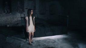Une belle jeune fille marchant dans une caverne de chambre noire Fond foncé projet social Long cheveu densité effrayé banque de vidéos