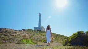 Une belle jeune fille, regarde un phare, dans un chapeau de paille Concept : récréation, belle vue, liberté, voyage et banque de vidéos