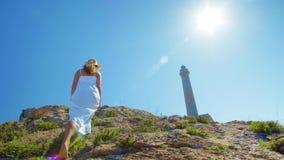 Une belle jeune fille, regarde un phare, dans un chapeau de paille Concept : récréation, belle vue, liberté, voyage et clips vidéos