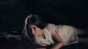 Une belle jeune fille se réveille Fond foncé projet social Long cheveu Feuilles de soie Plan rapproché confus banque de vidéos