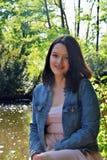 Une belle jeune fille se tient dehors à côté de l'eau photos stock