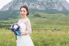 Une belle jeune mariée caucasienne avec un bouquet de mariage des fleurs dans des ses mains Photo libre de droits