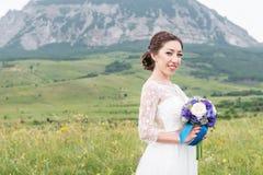Une belle jeune mariée caucasienne avec un bouquet de mariage des fleurs dans des ses mains Photographie stock
