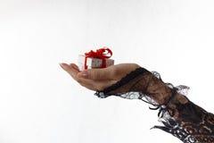 Une belle main femelle dans le gant noir de dentelle tient un boîte-cadeau avec le ruban rouge Images stock