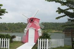 Une belle maison rose à côté d'un lac Photo libre de droits