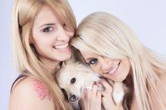 Une belle mode d'amies de femme, tenant le chien dedans Images stock