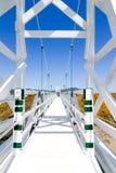 Une belle passerelle de suspension blanche avec le ciel bleu Image libre de droits