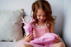 Une belle petite fille 4 années dans une robe rose joue avec les cerfs communs roses L'atmosphère de l'enfance Photo stock