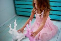 Une belle petite fille 4 années dans une robe rose joue avec les cerfs communs roses L'atmosphère de l'enfance Photographie stock