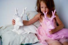 Une belle petite fille 4 années dans une robe rose joue avec les cerfs communs roses L'atmosphère de l'enfance Image libre de droits