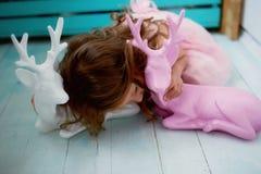 Une belle petite fille 4 années dans une robe rose joue avec les cerfs communs roses L'atmosphère de l'enfance Images stock