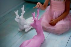 Une belle petite fille 4 années dans une robe rose joue avec les cerfs communs roses L'atmosphère de l'enfance Photo libre de droits