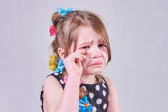 Une belle petite fille, avec une expression triste, pleure et l'essuie des larmes avec ses mains photos stock
