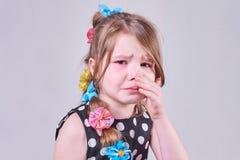 Une belle petite fille, avec une expression triste, pleure et l'essuie des larmes avec ses mains photos libres de droits