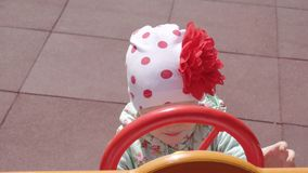 Une belle petite fille caucasienne jeux de 3 années sur un nouveau et multicolore terrain de jeu moderne une journée de printemps clips vidéos