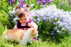 Une belle petite fille ukrainienne jouant sur une pelouse avec un chat de minerai photographie stock