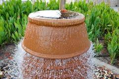 Une belle petite fontaine sous forme de vase brun, une cruche avec des gouttes de l'eau en baisse sur la position colorée de pier photographie stock libre de droits