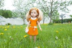 Une belle poupée avec la robe orange se tenant sur l'herbe verte dans le jardin images stock