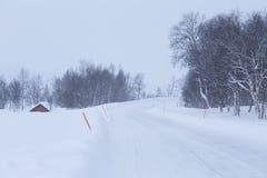 Une belle route blanche par la forêt en Norvège centrale avec des poteaux de sécurité Photos stock