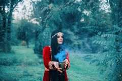 Une belle sorcière a préparé une boisson d'amour La tasse produit la fumée bleue magique Une femme essaye d'enchanter oriental photos libres de droits