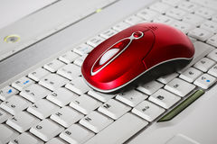 Une belle souris sans fil rouge sur le clavier blanc d'un ordinateur portable Photo stock