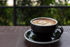 Une belle tasse de café d'art de Latte sur la table près du jardin photographie stock libre de droits