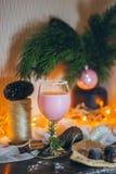 Une belle toujours scène de la vie dans l'humeur de Noël avec un verre de boisson et de bonbons roses sur les lumières de Noël et Images libres de droits