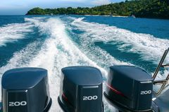 Une belle traînée mousseuse d'un bateau avec trois moteurs puissants, partant de la plage de banane de Coral Koh He Island, thaïl photo stock
