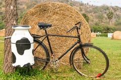 Une bicyclette noire d'homme de lait avec le récipient en acier de lait au fond Photo libre de droits