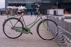 Une bicyclette verte avec un panier est garée seule dans une longue chambre photographie stock libre de droits